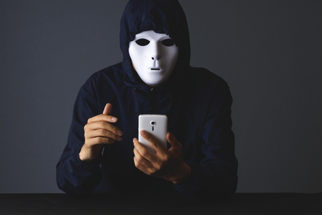 masked_man_using_smartphone